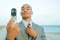 Businessman photographing self with cell phone at the beach, smiling, adjusting tie