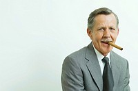 Businessman smoking cigar, smiling at camera, portrait