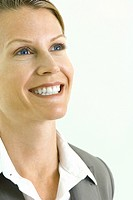 Businesswoman smiling, looking up, cropped portrait