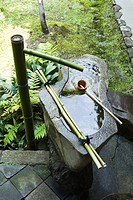 Stone water fountain with bamboo spigot and ladle