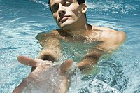 Man in swimming pool with eyes closed, scooping water with hands