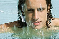 Man in swimming pool, looking at camera through splashing water, close-up