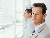 Two business men standing by window,focus on men looking at camera