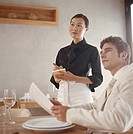 Waitress taking order from young man in restaurant