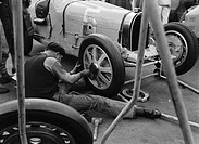 Robert Aumaitre working on Bugatti 1500 racing car wheel, Berlin, 1933.Photograph by Zoltan Glass. Frenchman Robert Aumaitre, known as 'Le Grand Rober...