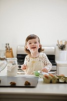 Portrait of young girl 2-3 cooking in kitchen, smiling