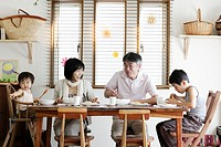 Couple with son 8-9 years and baby boy 18-24 months eating at dining table