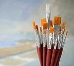Single white paintbrush sticking out from large group of orange brushes