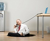Businessman sitting in hole of wooden floor, using landline phone