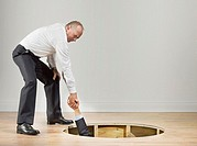 Businessman pulling man out from hole of wooden floor