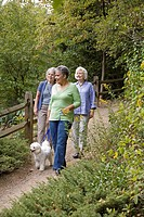 Three senior women with dog walking along path in garden