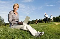 A businesswoman using a laptop on a golf course