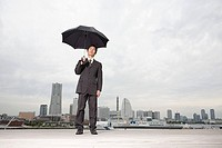 A businessman holding an umbrella
