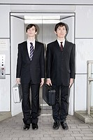 Portrait of businessmen holding briefcases