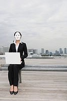 Businesswoman wearing a mask using a laptop