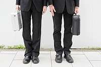 Businessmens legs and holding briefcases