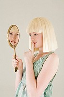 Young woman looking in mirror (thumbnail)