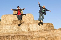 Boys jumping off bales of hay