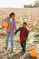 A boy and his grandmother in a field of pumpkins