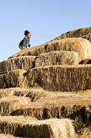 A girl climbing bales of hay