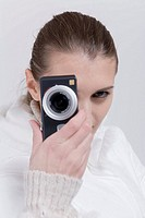 Woman holding digital camera on her face