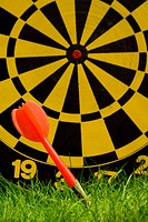 Close_up of dart with dartboard on grass