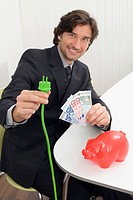 Man holding green plug and banknotes
