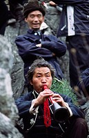 Long horn Miao man with trumpet during New Year celebrations, Guizhou, China