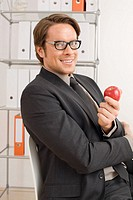 Businessman holding an apple, portrait