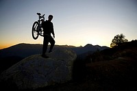 Man carrying bike over rock