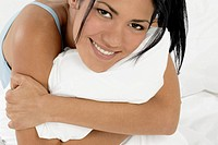 Smiling young woman hugging pillow