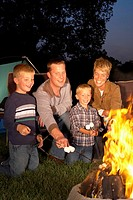 Family with two sons 4_6 years roasting marshmallows around campfire