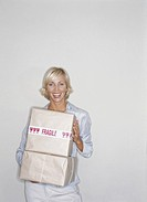 Young woman holding packages, smiling, portrait