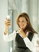 Smiling businesswoman photographing self with camera phone