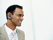 Business man wearing hands free device,smiling