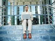 Portrait of business man using laptop sitting on steps outside building,low angle view