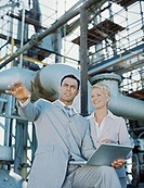 Business man and woman at oil refinery,smiling,man holding laptop
