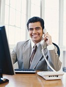 Businessman using computer and telephone, smiling
