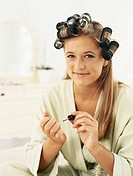 Young woman with hair rollers applying nail varnish, smiling, portrait