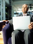 Business man using laptop sitting in bar