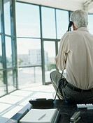 Senior man using phone in office,sitting on desk,rear view