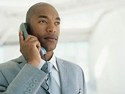 Mid adult businessman using phone,looking away,close_up