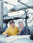 businessman and oil refinery worker leaning on pipeline system,discussing blueprints