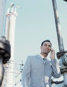Business man talking on mobile phone,smiling,at oil refinery