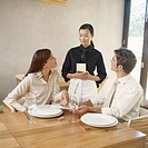 Waitress taking order from young couple in restaurant