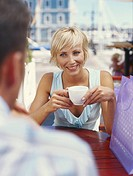 Couple in restaurant, focus on woman holding coffee cup