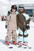 Brother and sister 6-7 in ski-wear outside resort, portrait