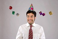 Young man wearing party hat, small gifts mid air