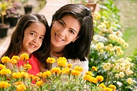 mother and daughter with flowers, smiling at camera