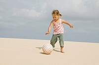 young girl kicking ball on sandy beach
